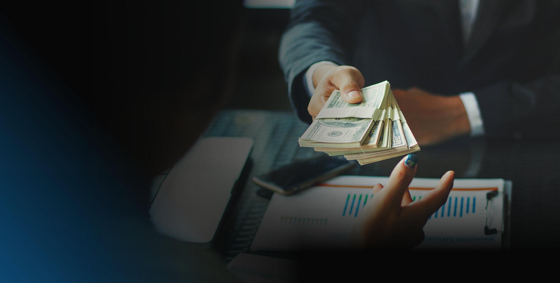 two people handing cash